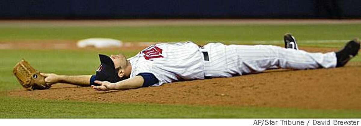 Minnesota Twins pitcher Nick Blackburn lays on the pitching mound after a ball hit by New York Yankees' Bobby Abreu grazed off his glove and hit him in the nose in fifth inning Sunday, June 1, 2008 in Minneapolis.