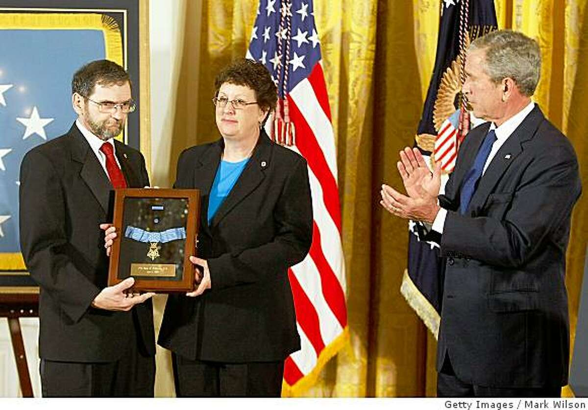 WASHINGTON - JUNE 02: U.S. President George W. Bush applauds after handing the Medal of Honor to Thomas and Romayne McGinnis parents of U.S. Army Spc. Ross Andrew McGinnis during a ceremony in the East Room at the White House, June 2, 2008 in Washington DC. Spc. McGinnis, 19, from Knox, Pennsylvania, was killed Dec. 4, 2006 when he jumped on a grenade to save other troops while on a combat patrol in Baghdad. (Photo by Mark Wilson/Getty Images)
