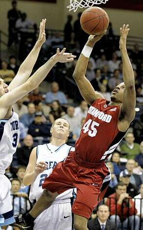 Stanford's Jeremy Green, right, shoots over the block of San Diego's Chris Manresa, left, as Matt Dorr, center, looks on during the first half of an NCAA college basketball game Friday, Nov. 13, 2009, in San Diego.  (AP Photo/Denis Poroy) Photo: Denis Poroy, AP