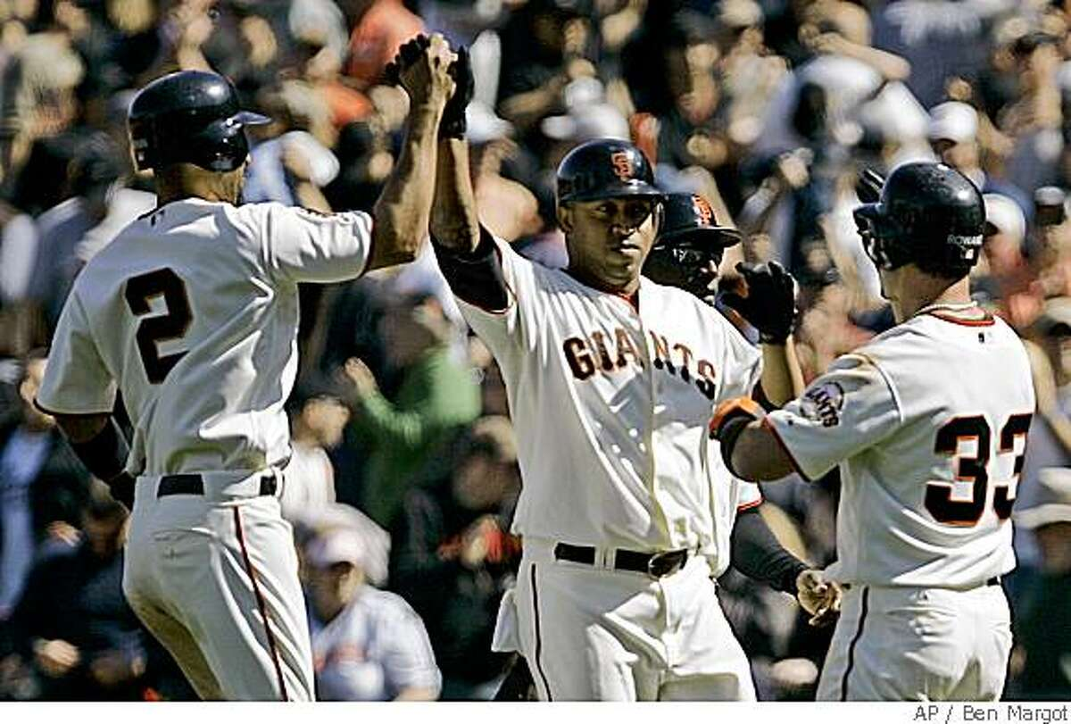 San Francisco Giants' Jose Castillo, center, is congratulated by teammates Randy Winn (2) and Aaron Rowand (33) after Castillo hit the game-winning RBI single off San Diego Padres' Trevor Hoffman during the 10th inning of a baseball game Sunday, June 1, 2008, in San Francisco. (AP Photo/Ben Margot)