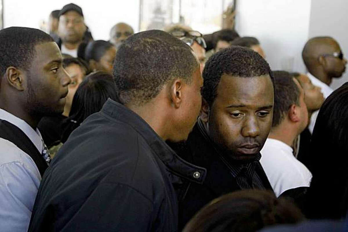 With only limited seating available, Karim Toney (rt), brother of Zoelina Williams waits to get into an Alameda County Superior Courtroom where Curtis Martin would later be charged for the slaying of Williams and her son Jashon on Tusesay Nov. 17, 2009 in Oakland, Calif.