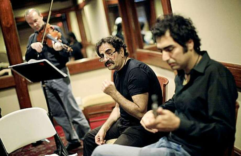 This photo taken Oct. 1, 2009 shows Iranian musician Shahram Nazeri, center, and his son Hafez, right, rehearsing  for an upcoming Los Angeles concert in Beverly Hills, Calif. By marrying the dainty lutes of the East with thrumming violas of the West in his latest symphony, composer Hafez Nazeri says he wants to create harmony between the U.S. and his native Iran.(AP Photo/Jae C. Hong) Photo: Jae C. Hong, AP
