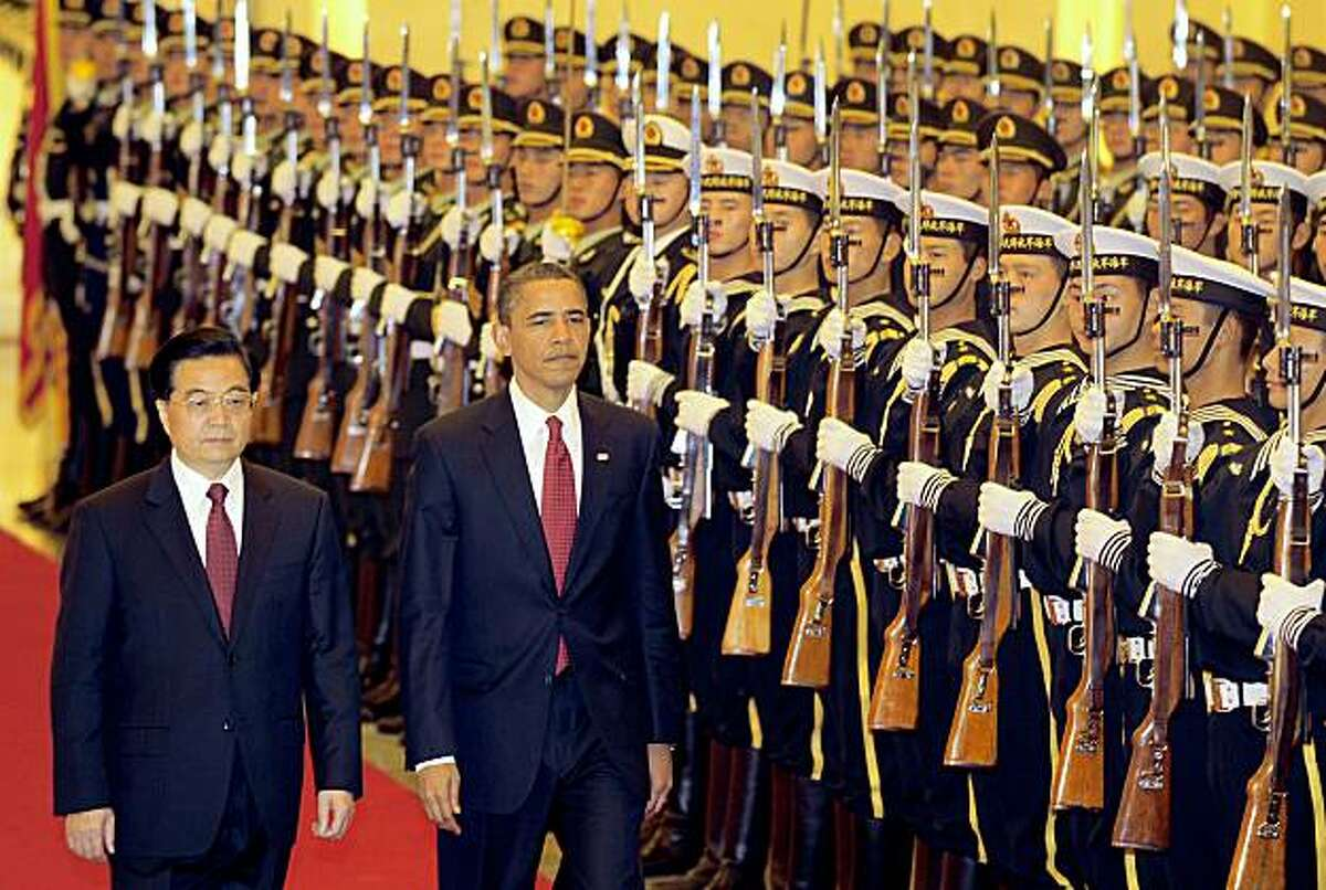 Visiting US President Barack Obama walks beside Chinese President Hu Jintao (L) during a review of the honour guard welcoming ceremony at the Great Hall of the People in Beijing on November 17, 2009. Obama was set to attack the formal business of his visit to China, sitting down with his opposite number Hu Jintao for talks centred on trade tensions and US calls for a stronger yuan. AFP PHOTO / Frederic J. BROWN (Photo credit should read FREDERIC J. BROWN/AFP/Getty Images)