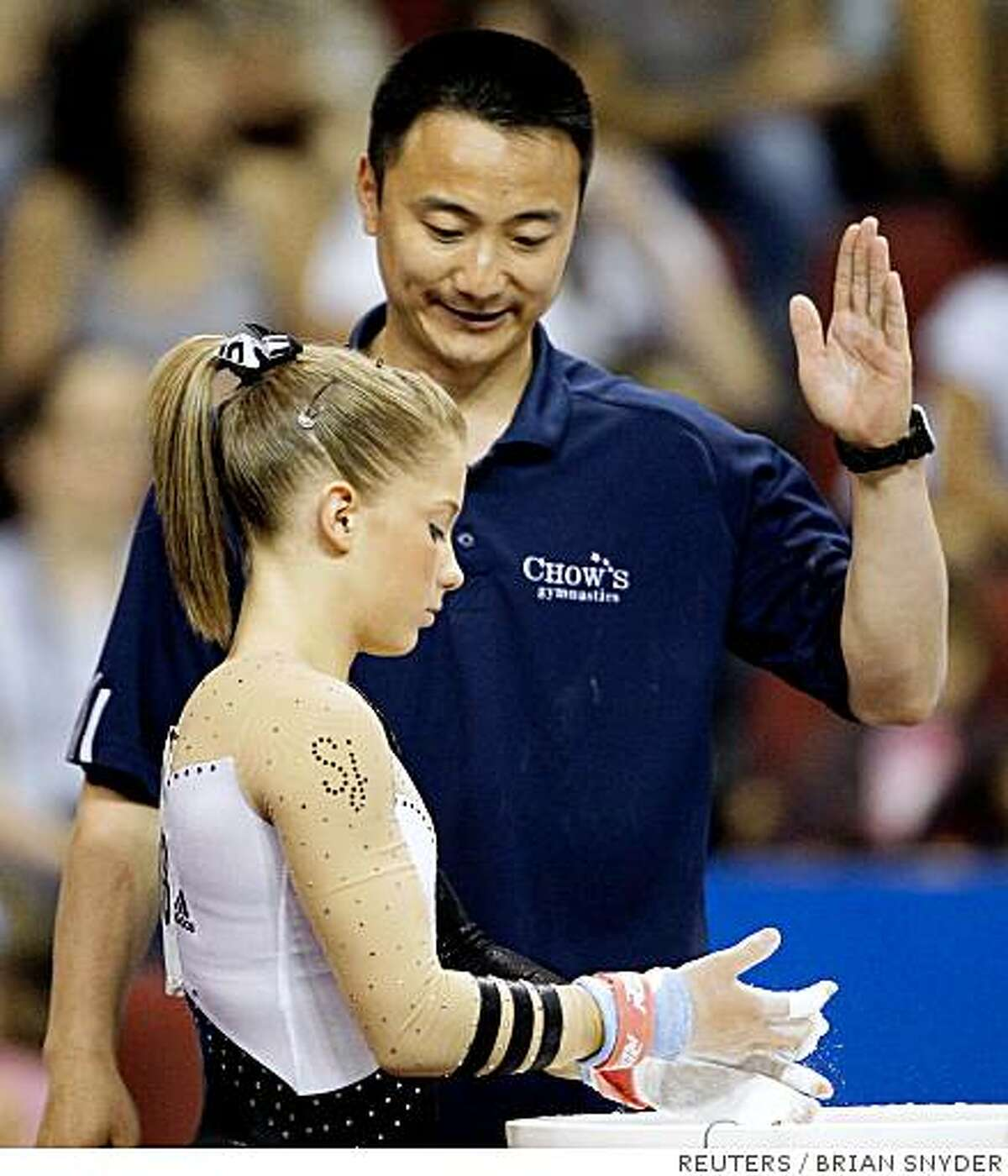 Shawn Johnson (front) listens to her coach Liang Chow before she competes on the uneven bars at the U.S. Women's Gymnastics Championships in Boston, Massachusetts, June 7, 2008. REUTERS/Brian Snyder (UNITED STATES)