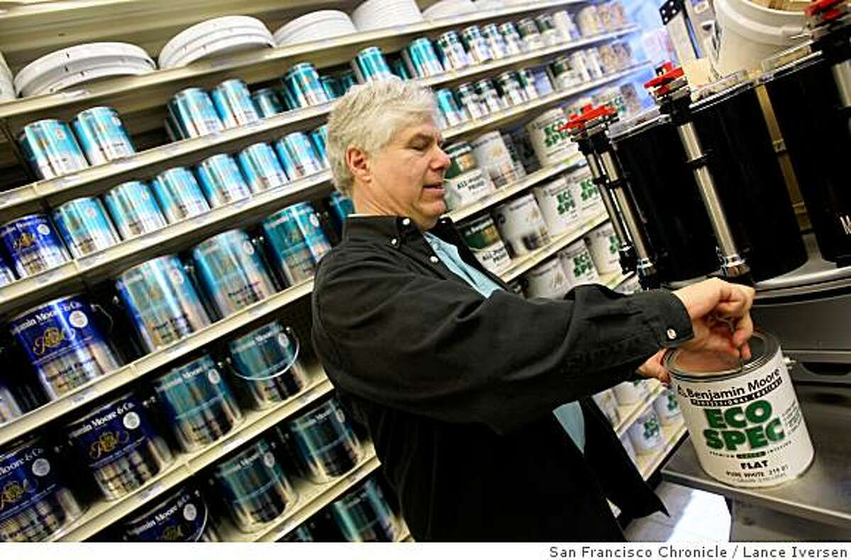 Rick Karp, owner of Cole Hardware, opens a can of eco-friendly paint. Among other things, Cole Hardware collects used paint, batteries and fluorescent light bulbs from customers for recycling. Chronicle photo by Lance Iversen