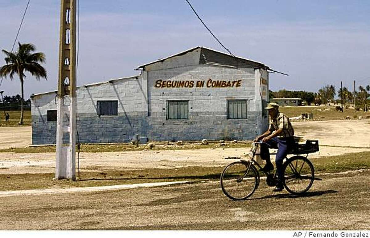 **APN ADVANCE FOR SUNDAY JUNE 8** A man rides his bicycle past a wall with a sign written on it that reads in Spanish: