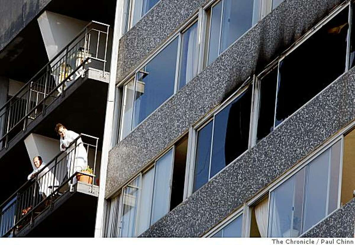 Residents stand on their balcony to see the damage, right, caused by a two-alarm fire that gutted an eighth-floor unit in an apartment building at Pacific Avenue and Franklin Street in San Francisco, Calif., on Friday, June 6, 2008.Photo by Paul Chinn / The Chronicle