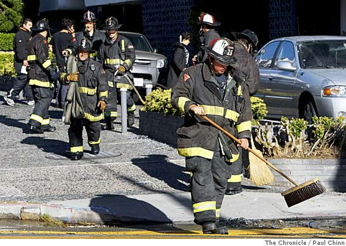 Firefighters sweep broken glass on the sidewalk after battling a two-alarm fire that gutted an eighth-floor unit in an apartment building at Pacific Avenue and Franklin Street in San Francisco, Calif., on Friday, June 6, 2008.Photo by Paul Chinn / The Chronicle