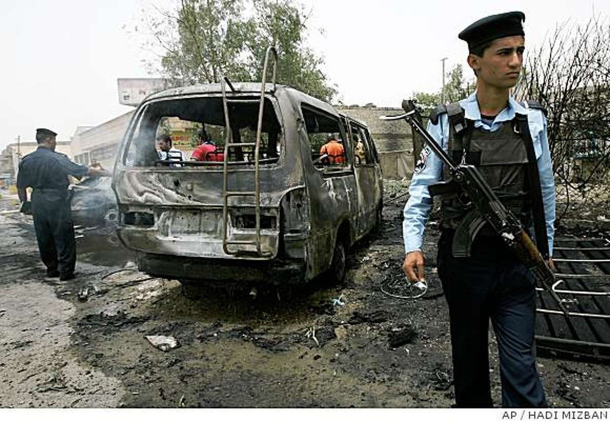 An Iraqi policeman stands at the site where a parked car bomb killed four people in Baghdad, Iraq, Monday, June 9, 2008. Police say the bomb targeted a passing police patrol in the Karrada neighborhood around 11:15 a.m. Monday. An army lieutenant was among the dead. At least seven other people were wounded, and many cars and shops were damaged. (AP Photo/ Hadi Mizban)