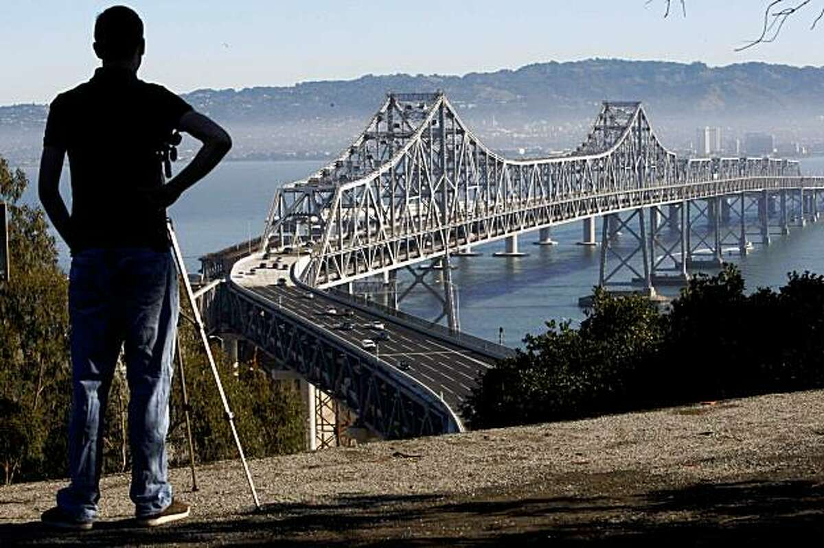 San Francisco State student Derek Highsmith watch with his video camera as commuter driver over the Bay Bridge since it reopened from emergency repairs on Monday, Nov. 2, 2009 in San Francisco, Calif.