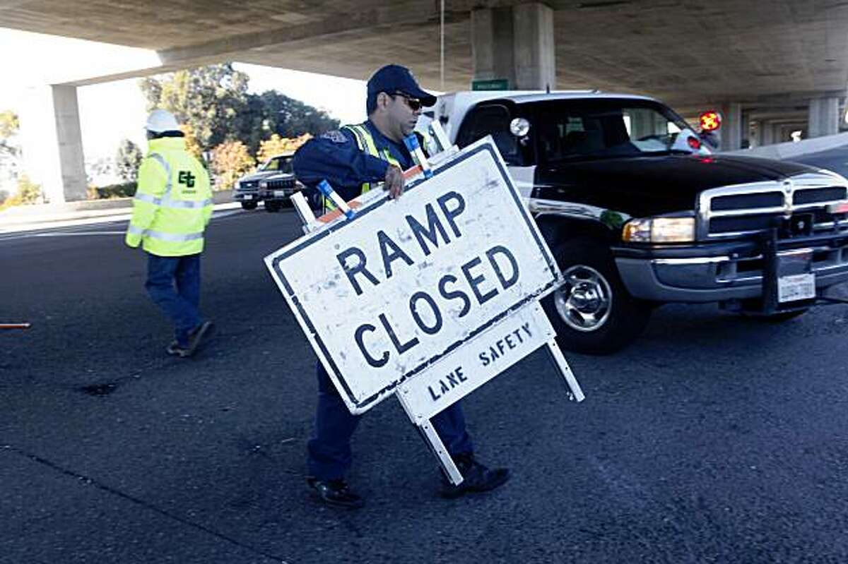 As drivers lineup in anticipation of the official reopening of the Bay Bridge, California Highway Patrol officer, Rod Rodriguez moves the final road block to the West Oakland entrance of the bridge on Monday, Nov. 2, 2009 in Oakland, Calif.