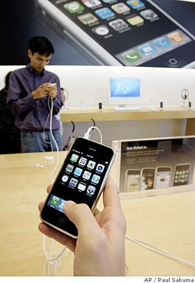 **FILE** In this July 24, 2007 file photo, customers examine Apple iPhones at an Apple store in Palo Alto, Calif..  Apple Inc. says its online stores in the U.S. and U.K. are sold out of the iPhone, a sign supplies are being winnowed ahead of the launch of the device's next generation that will feature faster Internet surfing speeds. (AP Photo/Paul Sakuma) Photo: Paul Sakuma, AP