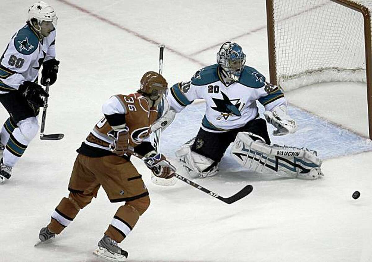 San Jose Sharks goalie Evgeni Nabokov (20), from Kazakhstan, deflects a shot by Carolina Hurricanes' Jussi Jokinen (36), from Finland, during the third period of an NHL hockey game in Raleigh, N.C., Sunday, Nov. 1, 2009. San Jose won 5-1. Sharks' Jason Demers (60) looks on at left. (AP Photo/Gerry Broome)