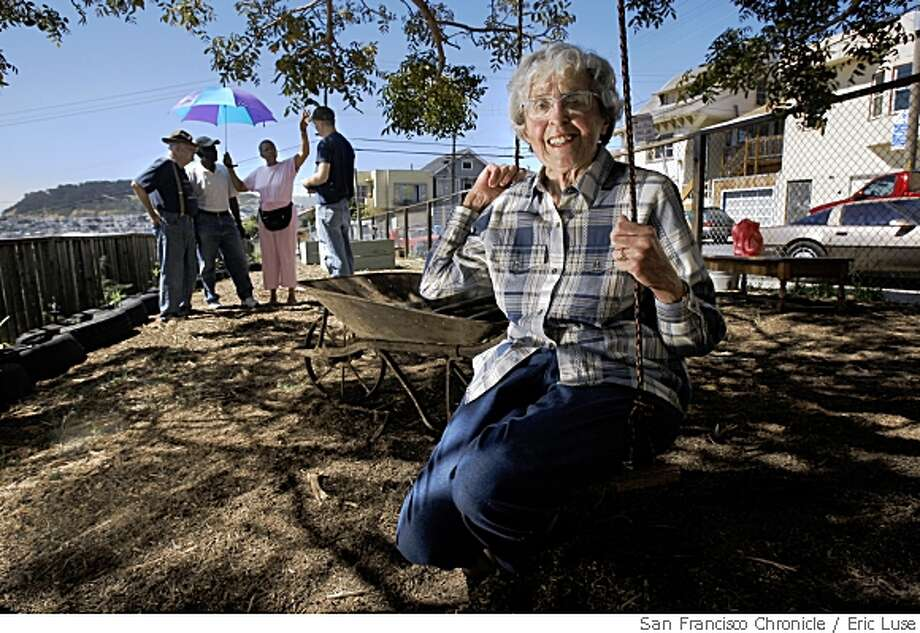 Among the founders is Irene Molinari,83, born on the block at The Latona Gardens just up from Third Street in the Bayview District of San Francisco photographed on Friday May 16, 2008  is now a new thriving garden after decades of being the neighborhood dump. Behind Molinari is a wheelbarrow she donated to the graden she's had since childhood and  neighbors active in working the garden. Photo by Eric Luse /  San Francisco Chronicle Photo: Eric Luse, SFC