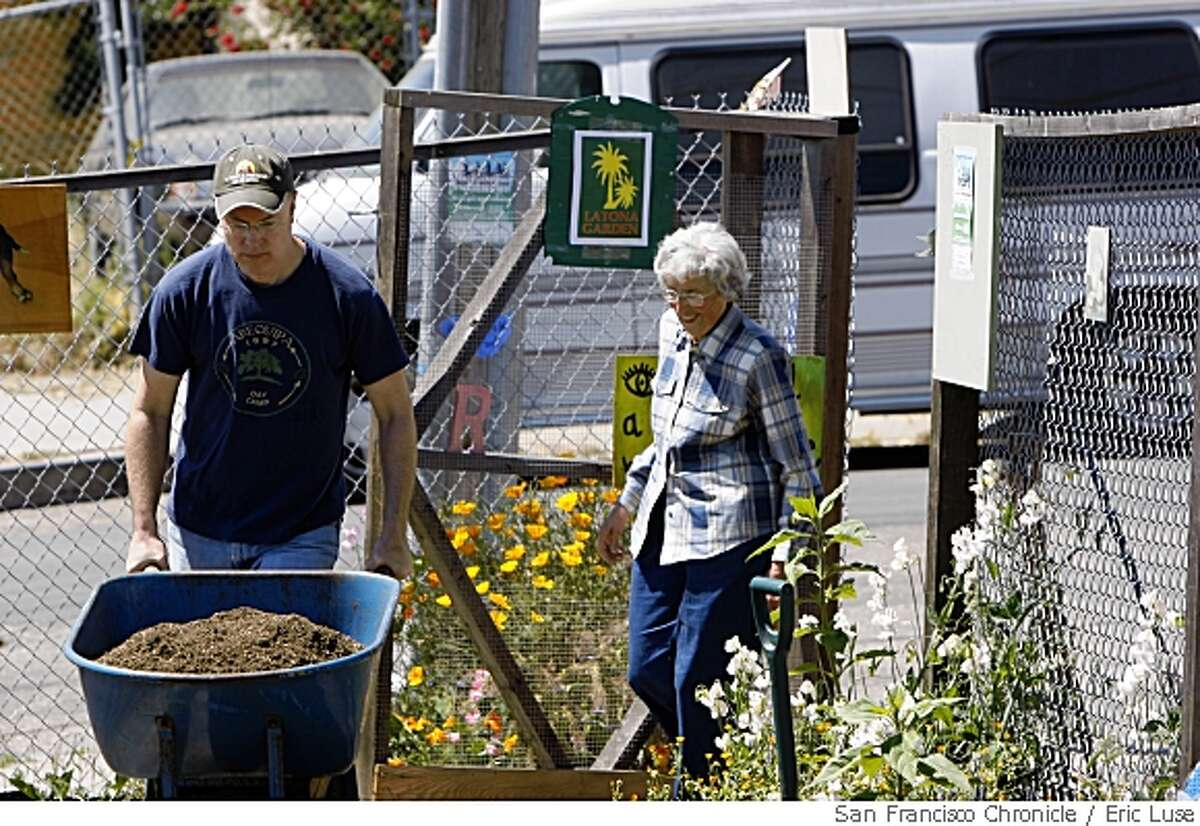 FILE PHOTO: Jeffrey Betcher and neighbors pitch in to move fresh compost to The Latona Gardens just up from Third Street in the Bayview District of San Francisco photographed on Friday May 16, 2008. Just behind him is Irene Molinari,83, in the new thriving garden after decades of being the neighborhood dump.