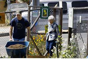 Co-Founder Jeffrey Betcher and neighbors pitch in to move fresh compost  to The Latona Gardens just up from Third Street in the Bayview District of San Francisco photographed on Friday May 16, 2008. Just behind him is Irene Molinari,83, in the new thriving garden after decades of being the neighborhood dump.  Photo by Eric Luse /  San Francisco Chronicle