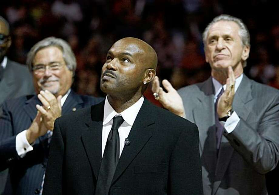 Former Miami Heat guard Tim Hardaway , center, looks up as his jersey is hoisted to the ceiling during a number retirement ceremony before an NBA basketball game between the Heat and the New York Knicks, Wednesday, Oct. 28, 2009 in Miami. Micky Arison, left, Heat managing general partner, and Pat Riley, right, president of the Heat and Hardaway's former coach, applaud. (AP Photo/Wilfredo Lee) Photo: Wilfredo Lee, AP