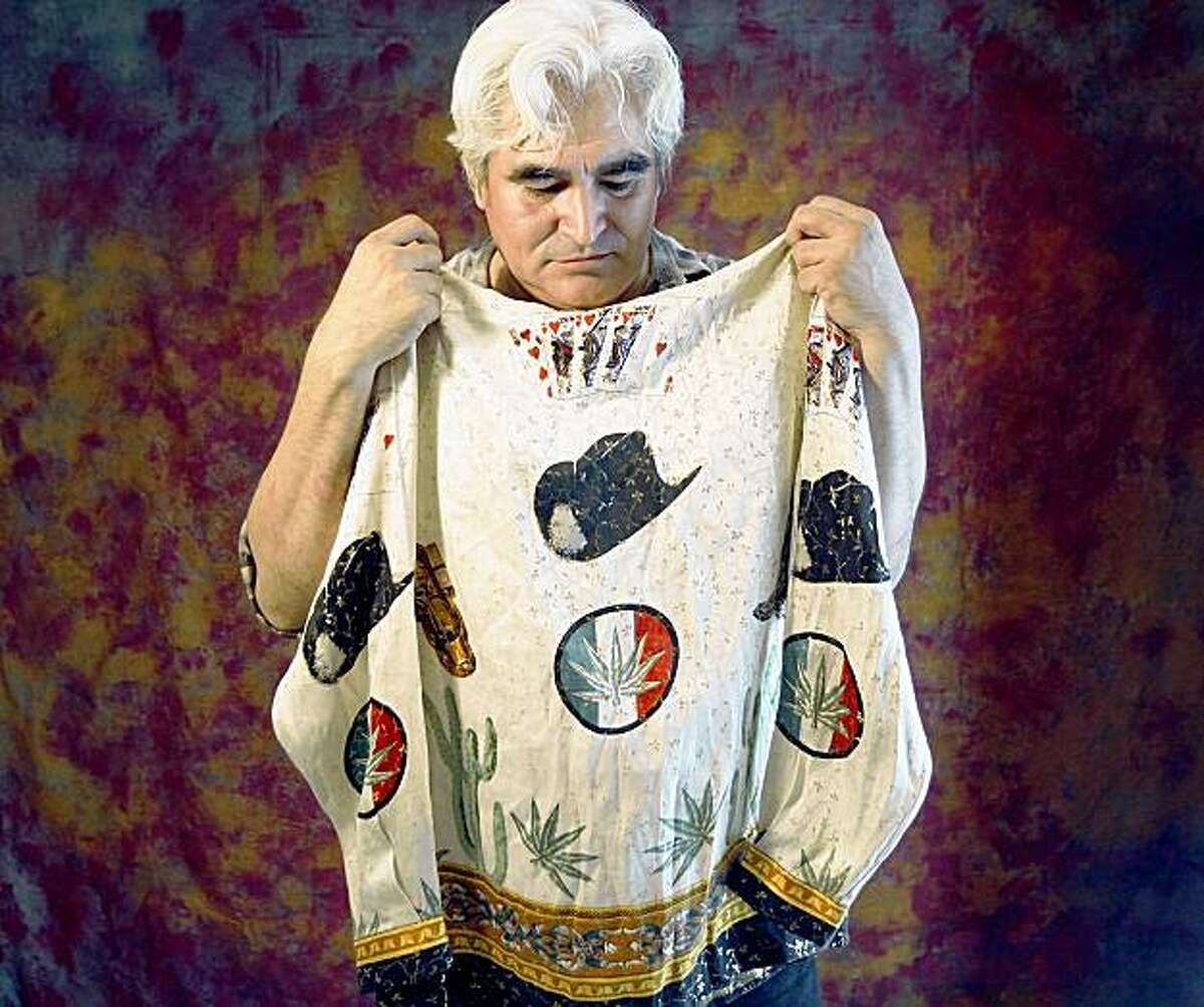 MEXICO PAINTER: Artist Jose Espinoza, 51, holds a silk party shirt adorned with symbols of Sinaloa's drug culture. Illustrates MEXICO-PAINTER (category i) by Tracy Wilkinson (c) 2009, Los Angeles Times. Moved Saturday, Oct. 24, 2009. (MUST CREDIT: Los Angeles Times photo by Don Bartletti.) Artist Jose Espinoza, 51, holds a silk party shirt adorned with symbols of Sinaloa's drug culture. Illustrates MEXICO-PAINTER (category i) by Tracy Wilkinson (c) 2009, Los Angeles Times. Moved Saturday, Oct. 24, 2009. (MUST CREDIT: Los Angeles Times photo by Don Bartletti.)