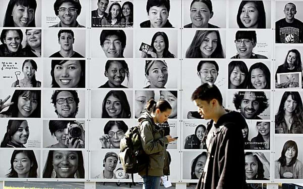 Students walk past a panel of photographs by photographer Christopher Irion depicting Cal students and staff on campus near Dwinelle Hall in Berkeley, Calif., on Thursday, Nov. 12, 2009.
