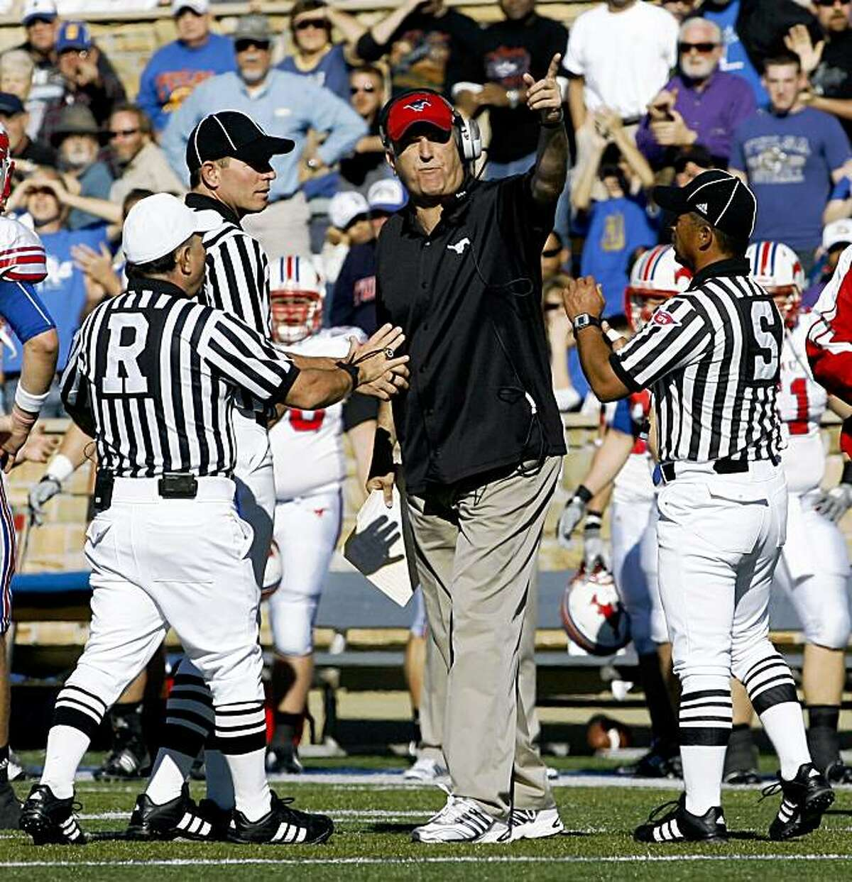 SMU hefad coach June Jones is escorted off the field by three officials during the third quarter of an NCAA college football game in Tulsa, Okla., on Saturday, Oct. 31, 2009. Jones had been trying to call a time out. He was given a penalty for coming onto the field. SMU defeated Tulsa, 27-13. (AP Photo/David Crenshaw)