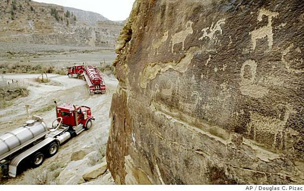 Tanker trucks pass petroglyphs Wednesday, April 30, 2008, in Nine Mile Canyon northeast of Wellington, Utah. It is still unclear exactly how the increased dust and continued use of a dust suppressant in the canyon will affect the rock art. (AP Photo/Douglas C. Pizac)