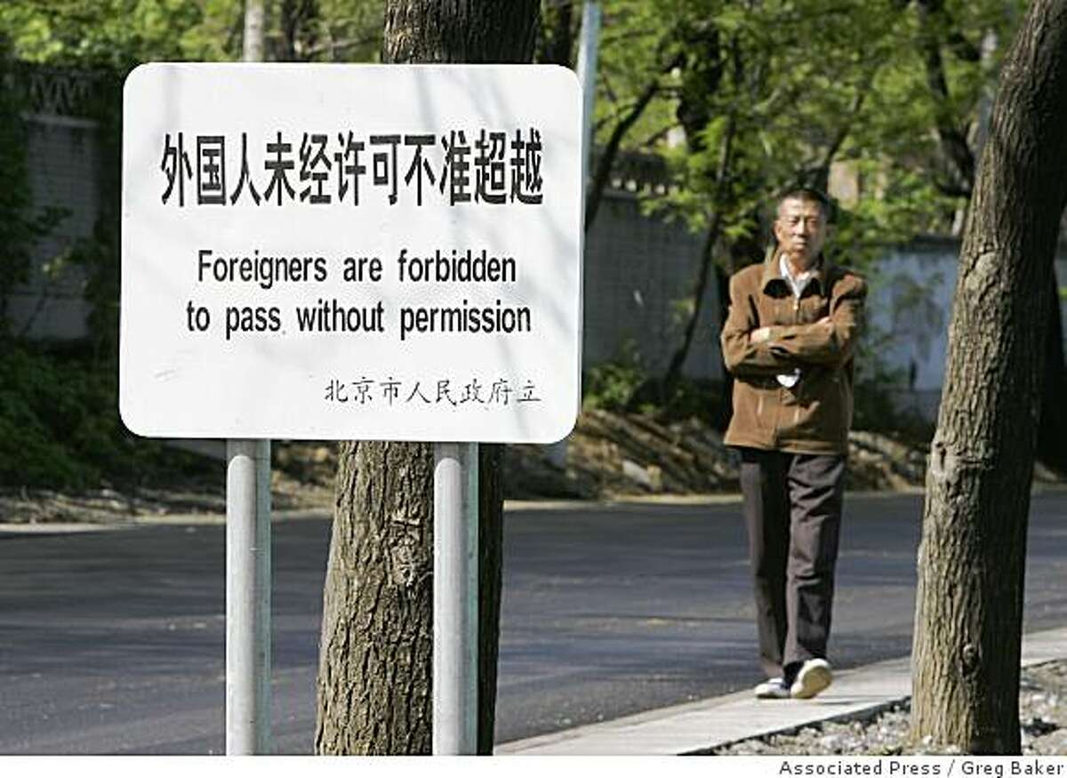 A resident walks past a sign which forbids foreigners to pass, on a public street near a military zone in Beijing Monday, April 21, 2008. Foreigners attending the Beijing Olympics better behave - or else. A nine-page document issued Monday, June 2, 2008 by the Beijing organizing committee spells out the do's and don'ts for foreigners visiting the Olympics. It also warns of punishments for those who misbehave during the Aug. 8-24 games. (AP Photo/Greg Baker)