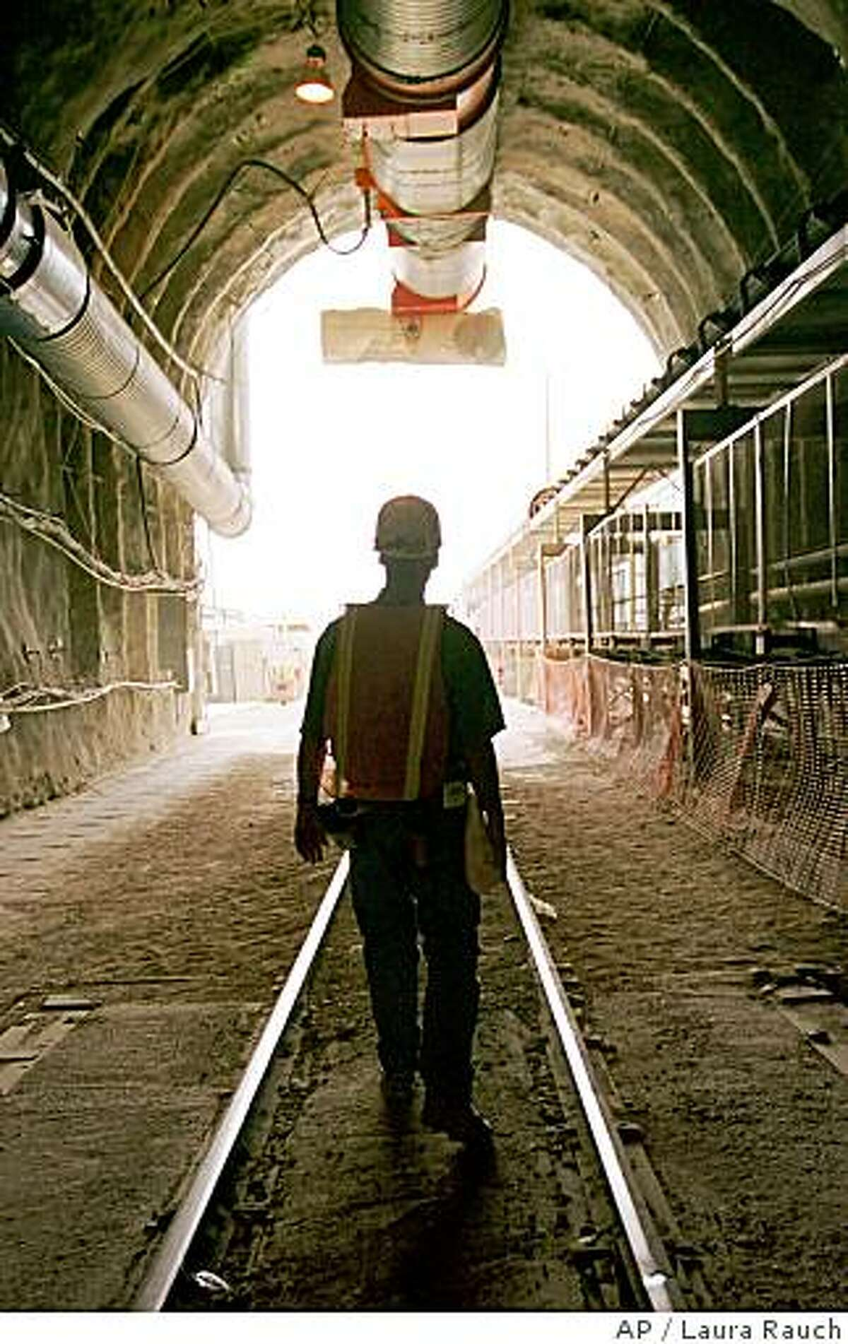 **FILE** In this May 9, 2000 file photo, a mining engineer walks out the front entrance tunnel at the Yucca Mountain Project at the Nevada Test Site. The Bush administration moved a step closer to building a nuclear waste dump at Yucca Mountain in Nevada on Tuesday, Juine 3, 2008, filing a formal application for a construction license. (AP Photo/Laura Rauch, File)