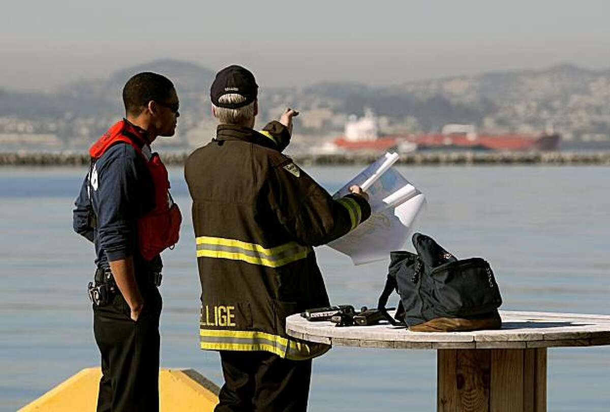 """Members of the Oakland Fire Marine & Hazardous Materials Unit, Martin Mazyck, (left) and Scott Hillige, stage from the former Alameda Naval Air Station, as they respond to an oil spill in San Francisco Bay, after the ship, """"Dubai Star"""" spilled bunker oil into the Bay South of the Bay Bridge near Alameda, Calif, on Friday October 30, 2009."""