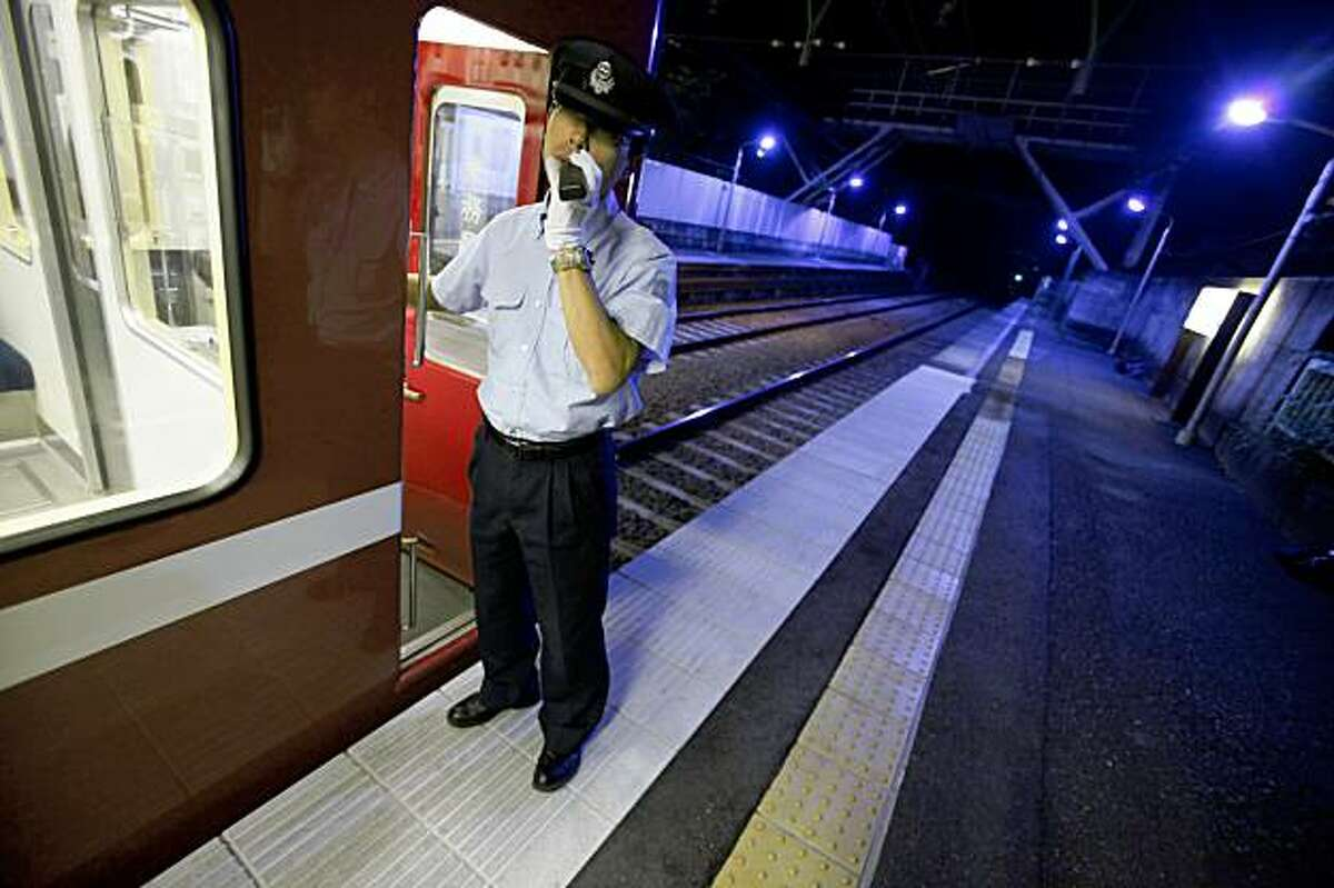 A train conductor of Keihin Electric Express Railway Co. Ltd., which operates in Tokyo and nearby Yokohama, alerts to passengers of closing the doors, with backdrop of the blue lights in the company's attempt to help deter suicides at Gumyoji station in Yokohama, west of Tokyo, Wednesday, Oct. 14, 2009. Alarmed by a rise in people jumping to their deaths in front of trains, Japanese railway operators are installing special blue lights above station platforms they hope will have a soothing effect and reduce suicides. (AP Photo/Itsuo Inouye)
