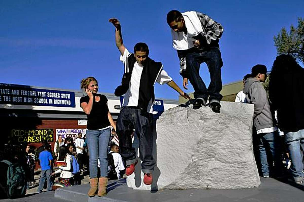 Armondo Zaragosa( left) and Carlos Esqueda jump off the rock in front of the Richmond High School as the community rally ends, Wednesday Oct. 28, 2009, in Richmond, Calif.