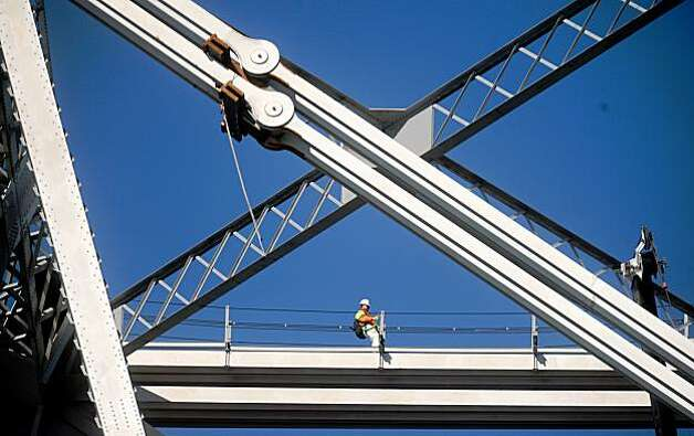 A worker walks below a damaged eyebar support on the Bay Bridge on Wednesday in San Francisco. The bridge remains closed in both directions following a support failure Tuesday evening. Photo: Noah Berger, Special To The Chronicle