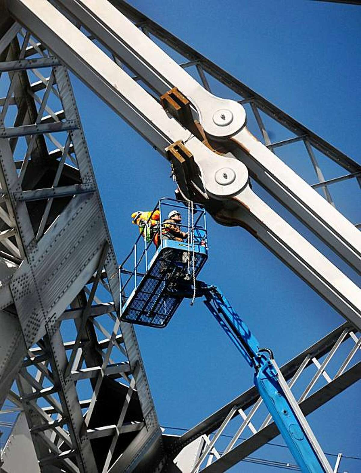 Workers inspect an eyebar support on the Bay Bridge on Wednesday. The bridge remains closed in both directions following a support failure Tuesday evening.
