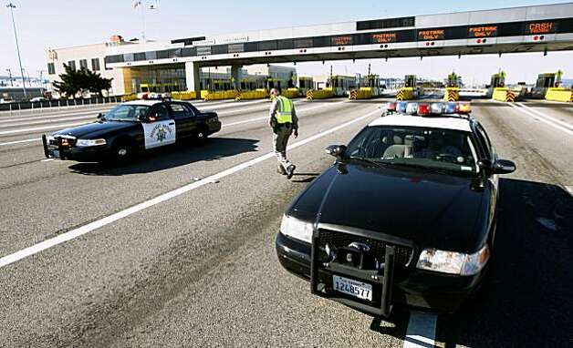 California highway patrol officer Rick Baller returns to his patrol car Wednesday on the approach to the tollbooths for the closed Bay Bridge. Photo: Lance Iversen, The Chronicle