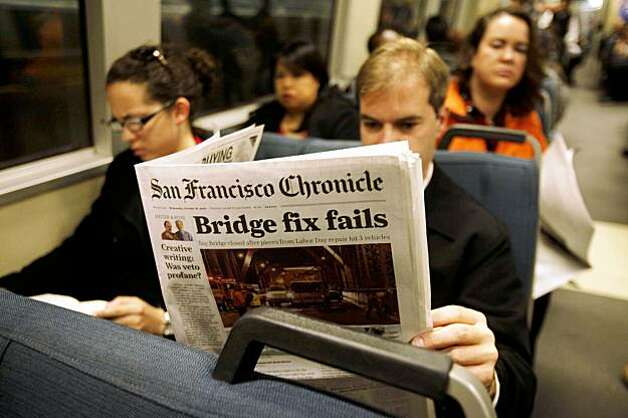 The morning after  the Bay Bridge was closed indefinitely for repairs, Jeremy Adams  checks the paper while riding BART to see if he will be able to get to work on Treasure Island on Wednesday. Photo: Mike Kepka, The Chronicle