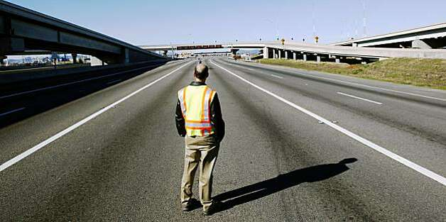 Cal-Trans employee Ben Strumwasser stands in the vacant number one lane on the approach to the Bay Bridge tollbooth on Wednesday. Photo: Lance Iversen, The Chronicle