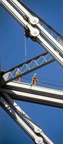 Workers attempt to repair an eyebar support, seen above them, on the Bay Bridge on Wednesday in San Francisco. The bridge remains closed in both directions following a support failure Tuesday evening. Photo: Noah Berger, Special To The Chronicle