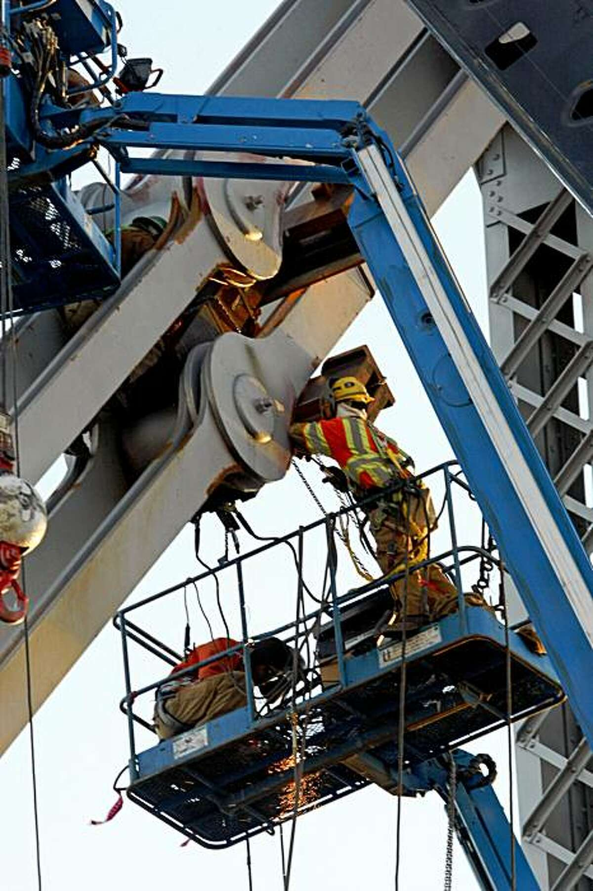 Ironworkers work on the saddle and tie-rods that failed on the Bay Bridge.
