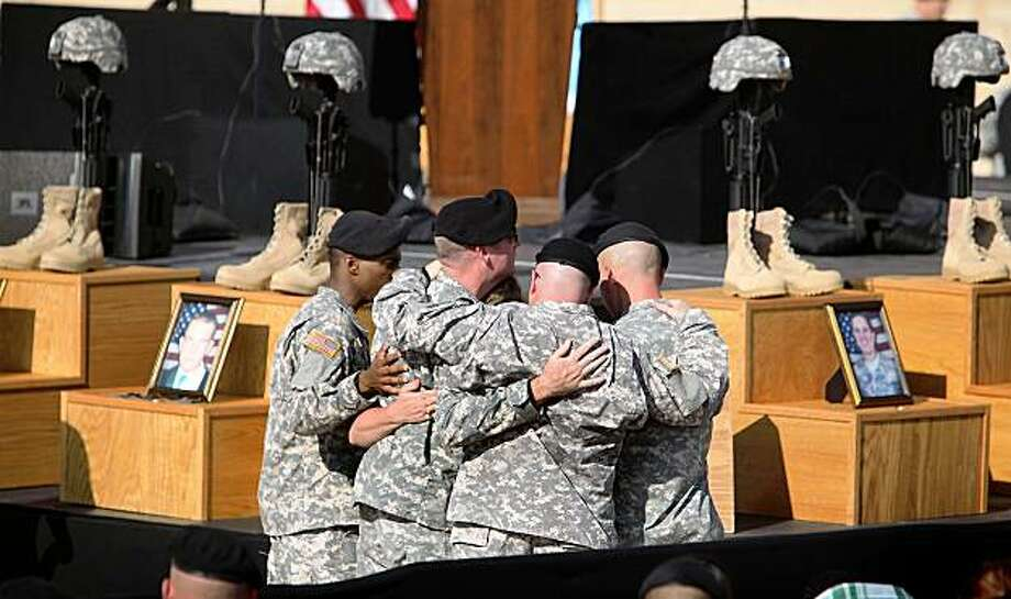 FORT HOOD, TX - NOVEMBER 10:  U.S. Army soldiers grieve together during the memorial service that U.S. President Barack Obama and first lady Michelle Obama attended in honor of the thirteen victims of the shooting rampage allegedly by U.S. Army Major Nidal Malik Hasan on November 10, 2009 in Fort Hood, Texas. Hasan, an army psychiatrist, is accused of killed 13 people and wounded 30 in a shooting at the military base on November 5, 2009.  (Photo by Joe Raedle/Getty Images) Photo: Joe Raedle, Getty Images