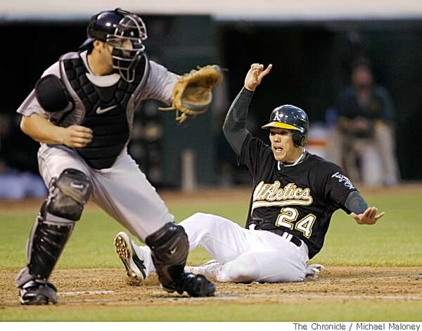 Kurt Suzuki beats the throw to Toronto catcher Rod Barajas to score on Jack Hannahan's double. Chronicle photo by Michael Maloney