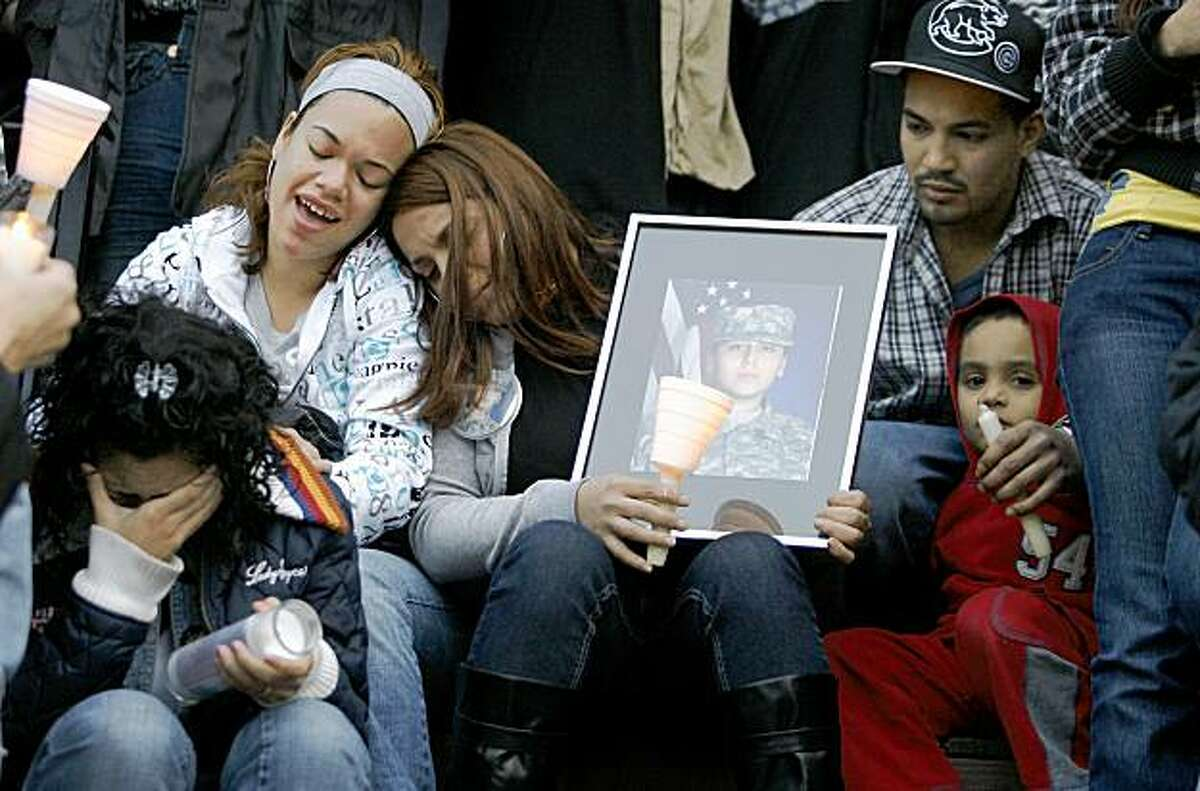 Family members listen to music during a vigil, in front of the home of Pvt. Francheska Velez, 21, in Chicago, Monday, Nov. 9, 2009. Velez, pregnant and preparing to return home, was one of the people killed in the Fort Hood shootings last week. (AP Photo/John Smierciak)