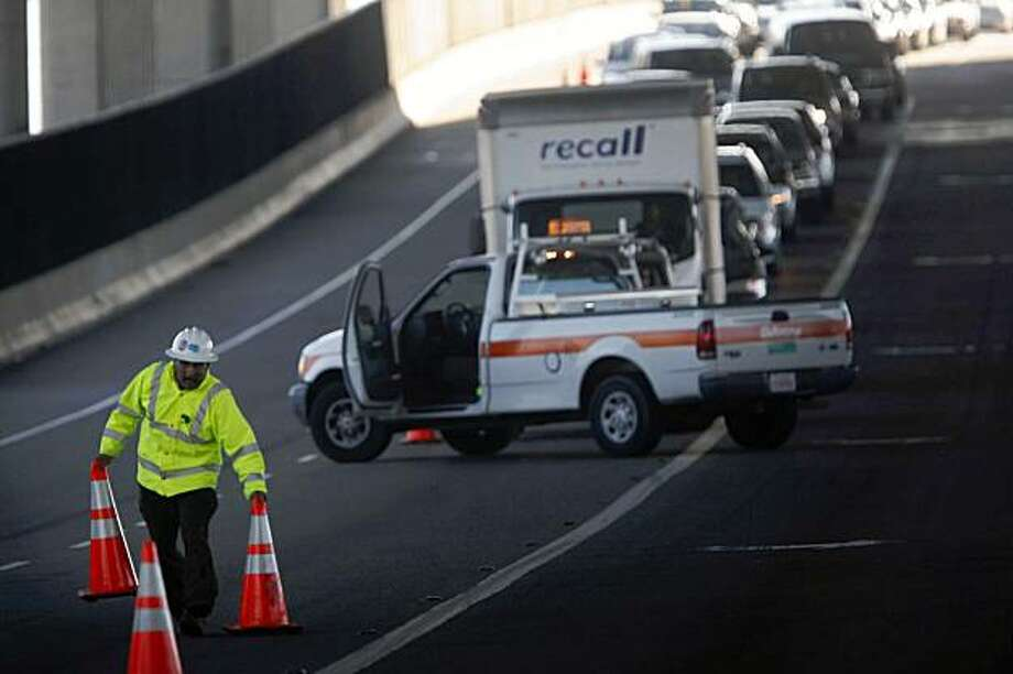 As drives lineup in anticipation of the official reopening of the Bay Bridge, A Caltrans safety officer Waqar Ahmed moves the final road blocks to the West Oakland entrance of the bridge on Monday, Nov. 2, 2009 in Oakland, Calif. Photo: Mike Kepka, The Chronicle