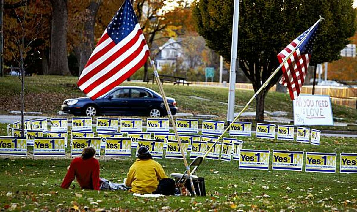American flags flap in the breeze by signs encouraging voters to vote against gay marriage, with a single sign, at right, representing the other side of the issue, the day before election day in Portland, Maine, on Monday, Nov. 2, 2009. Gay marriage legislation was approved by the Maine Legislature earlier in the year however Maine voters go to the polls on Tuesday where they will have the opportunity to become the first in the nation to approve gay marriage or vote against it.(AP Photo/Pat Wellenbach)