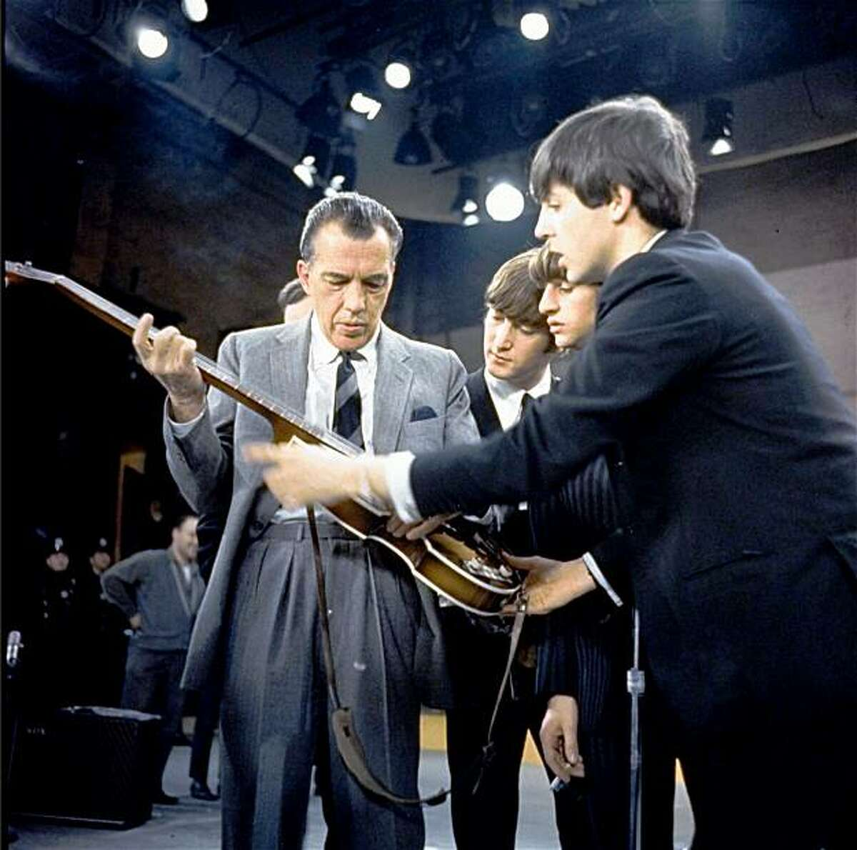 Three of the Beatles show a guitar to Ed Sullivan on stage Feb. 9, 1964 before their performance on his CBS television show in New York. From right are Beatles Paul McCartney, Ringo Starr and John Lennon.