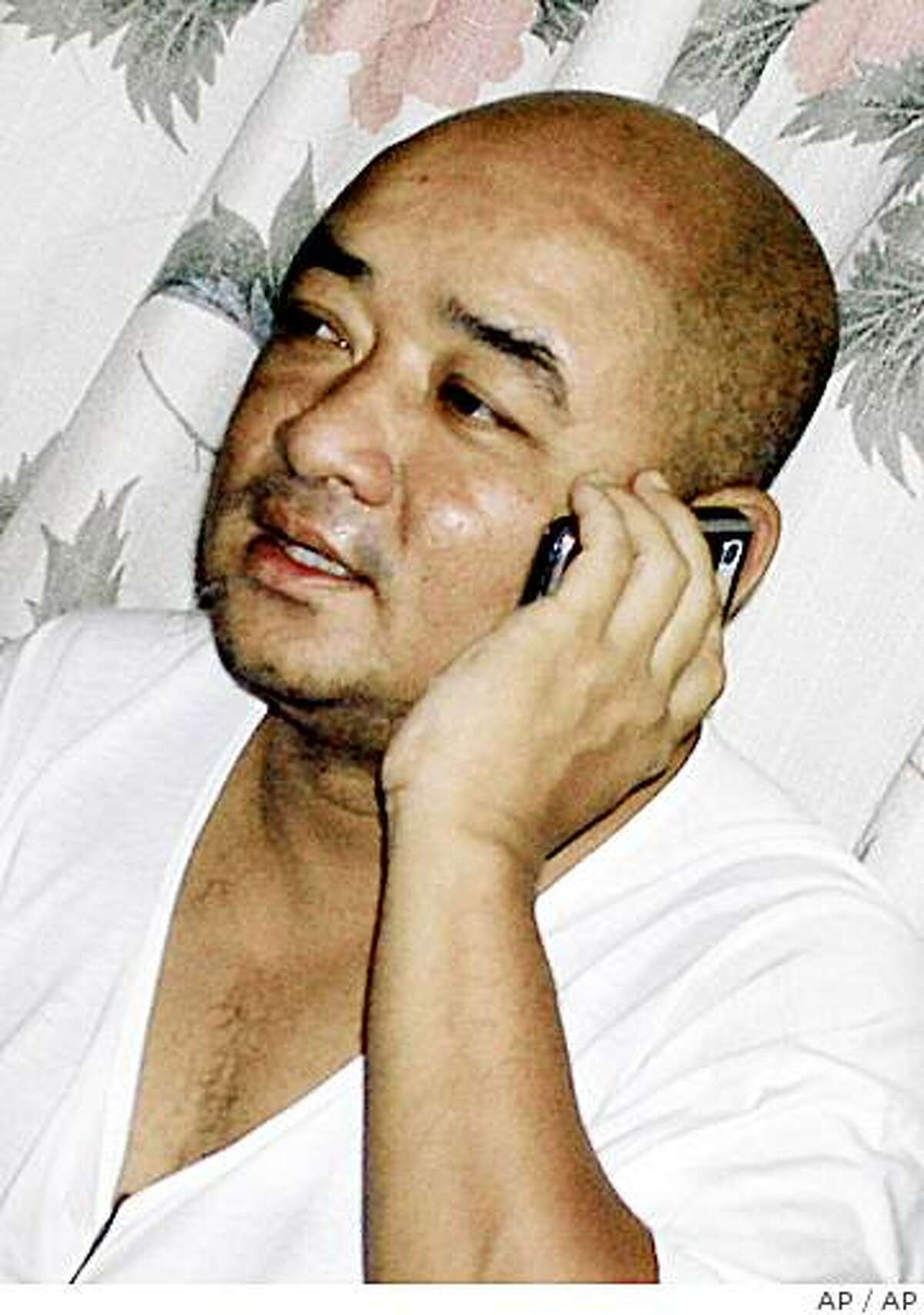 ** FILE ** In this May 18, 2006 file photo Myanmar comedian Maung Thura, better known by his stage name of Zarganar, talks on his mobile phone at his home in Yangon, Myanmar. Myanmar's most popular comic, known for his jibes against the military regime and recently for helping cyclone victims, has been taken from his home by police, family members said Thursday June 5, 2008. (AP Photo, FILE)