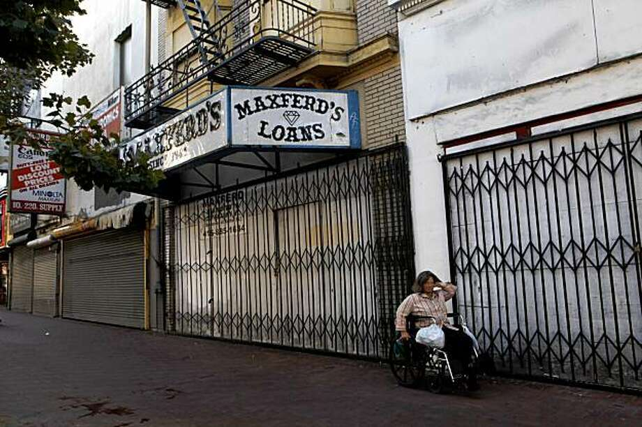 Empty store fronts and iron gates on Market Street on Friday Sep. 23, 2009 in San Francisco, Calif. could soon be replaced by giant eye catching billboards is Prop. D is passed in San Francisco. Photo: Mike Kepka, The Chronicle
