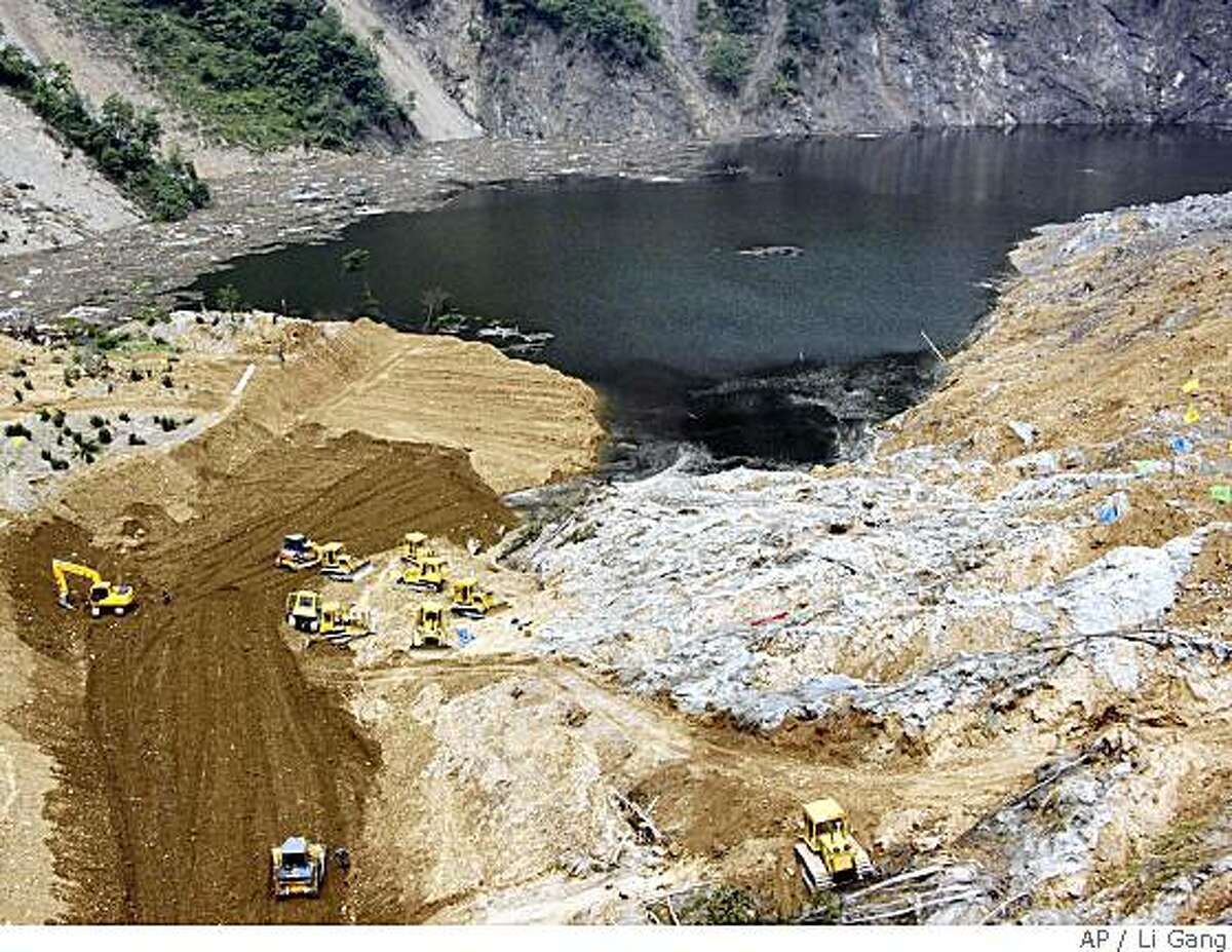 In this photo distributed by the official Chinese news agency, Xinhua, the major project of a sluice from the Tangjiashan Lake is completed at quake-induced Tangjiashan Lake in southwest China's Sichuan province, on Saturday May 31, 2008. (AP Photo/Xinhua, Li Gang)