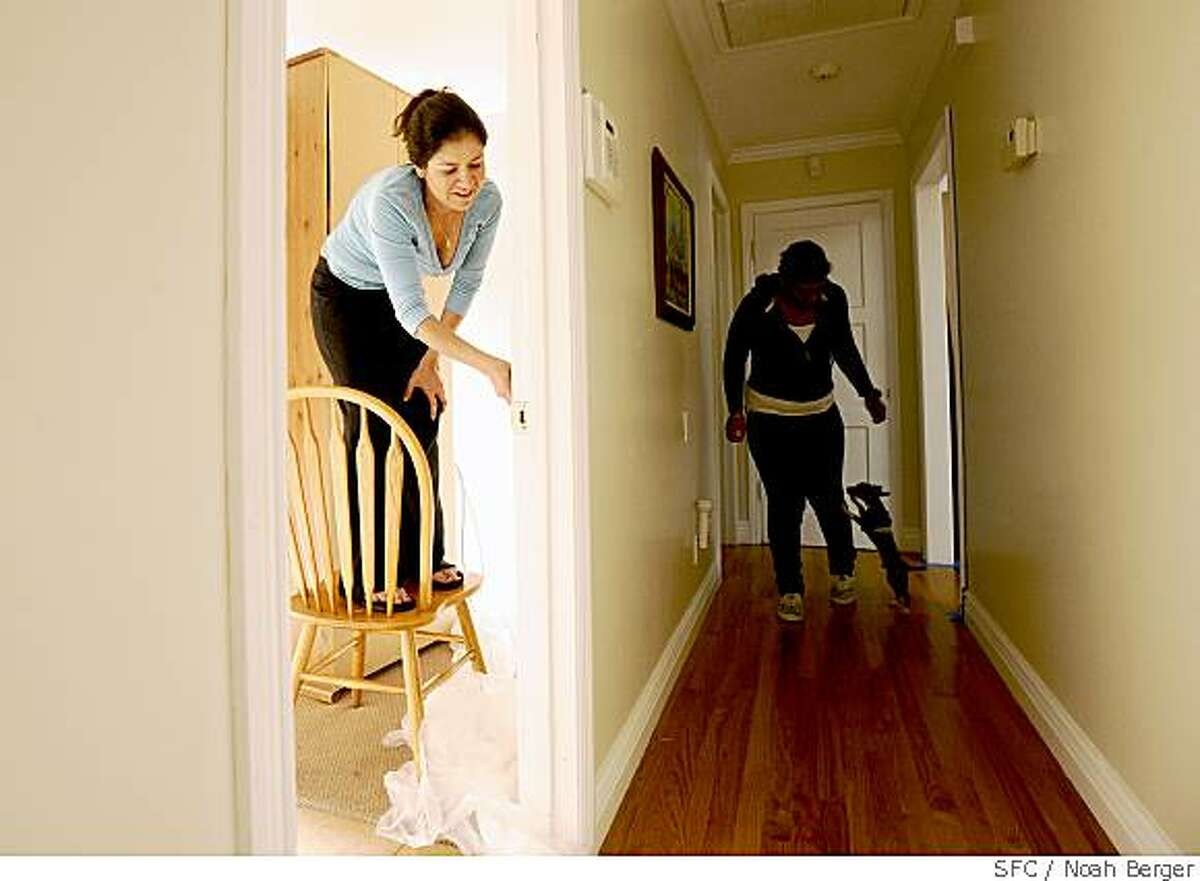 Tanya Orozco paints the guest room of her East Palo Alto, Calif., home on Friday, May 23, 2008, as her cousin Karina Fuller and Bam-Bam the Chihuahua make their way down the hall to help.