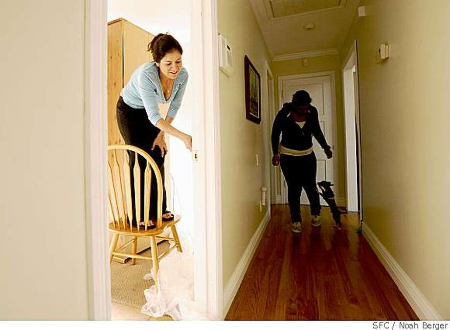 Tanya Orozco paints the guest room of her East Palo Alto, Calif., home on Friday, May 23, 2008, as her cousin Karina Fuller and Bam-Bam the Chihuahua make their way down the hall to help. Photo: Noah Berger, Special To The Chronicle