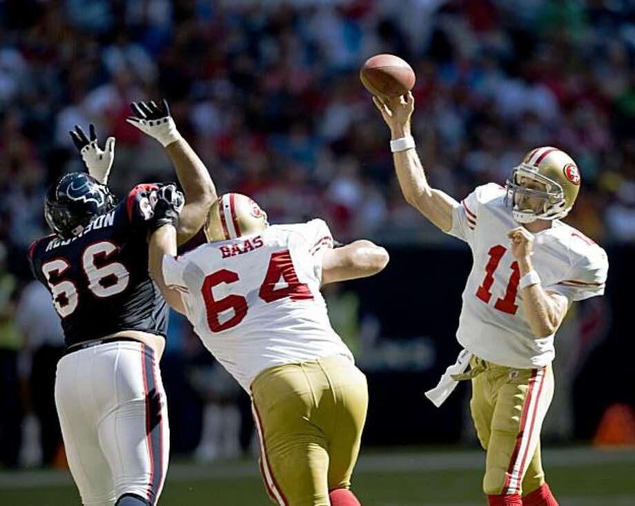 San Francisco 49ers quarterback Alex Smith (11) fires a touchdown pass as guard David Baas (64) blocks against Houston Texans defensive tackle DelJuan Robinson (66) during the fourth quarter of an NFL football game at Reliant Stadium, Sunday, Oct. 25, 2009, in Houston. The Texans won the game 24-21. Photo: Smiley N. Pool, Hearst Newspapers