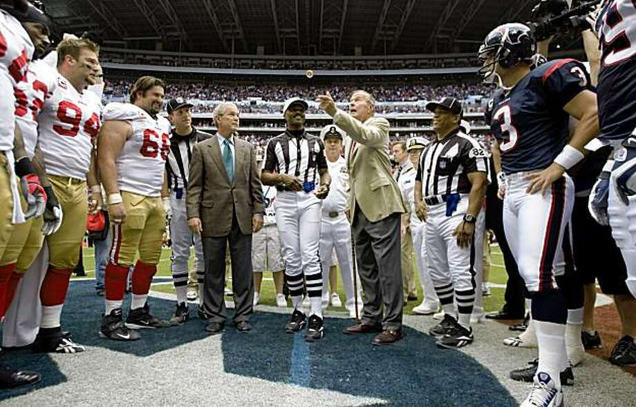 Former President George H.W. Bush, right, flips the coin as he and his son, former President George W. Bush participate in the coin toss before an NFL football game between the Houston Texans and San Francisco 49ers at Reliant Stadium Sunday, Oct. 25, 2009, in Houston. ( Brett Coomer / Chronicle ) Photo: Brett Coomer, Chronicle